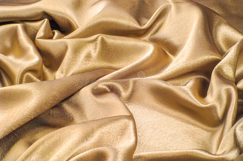 Fabric made of silk fabric metal thread metallic sheen gold. Just like looking at a stunning waterfall, this golden yellow Silk C royalty free stock photo
