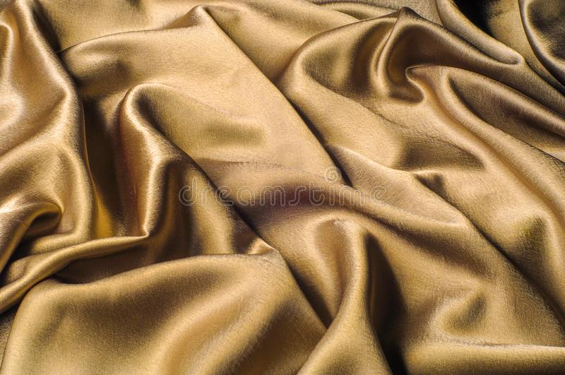 Fabric made of silk fabric metal thread metallic sheen gold. Just like looking at a stunning waterfall, this golden yellow Silk C. Harmeuse stands alone stock photo