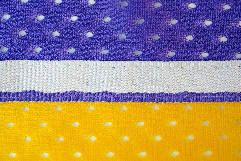 Fabric made of yellow and purple polyester background with white ribbon in the middle royalty free stock image