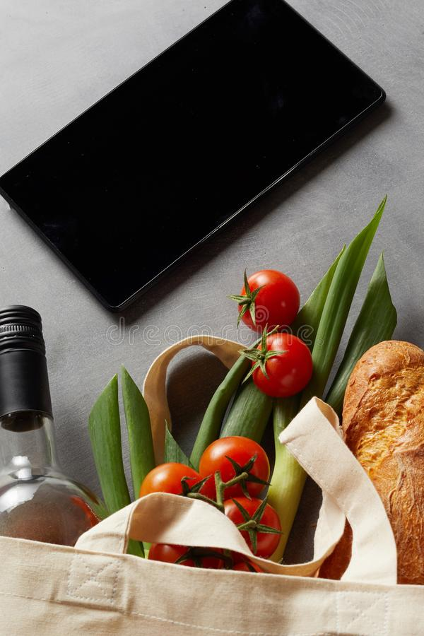 Fabric shopping bag with groceries and tablet stock image