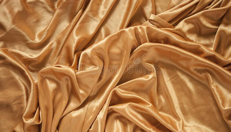 Fabric silk texture for background. Gold silk texture of satin abstract background stock photography
