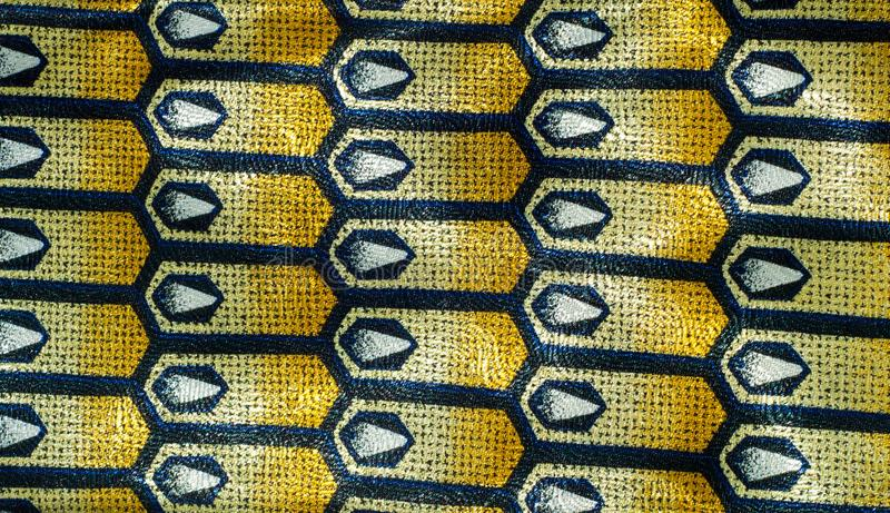 Fabric silk texture, background, yellow with black pattern. Texture of silk fabric. background. costume jewelery chain with the emblem of Paris stock photo