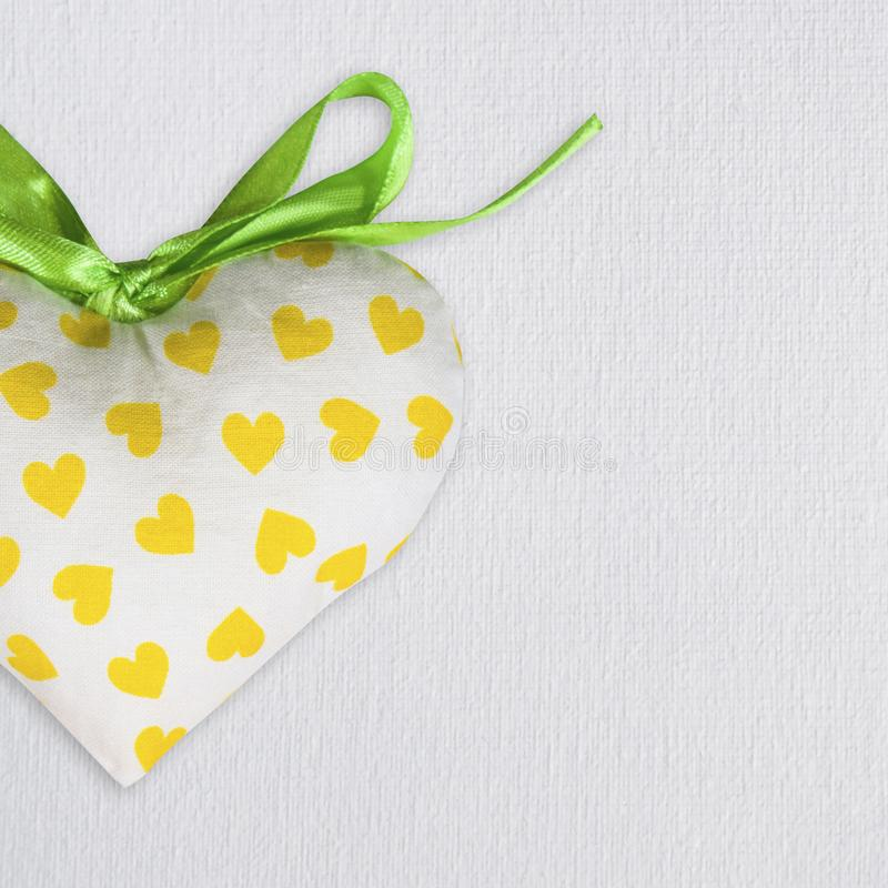 Fabric toy heart on white canvas background. St. Valentine`s Day postcard template royalty free stock photo