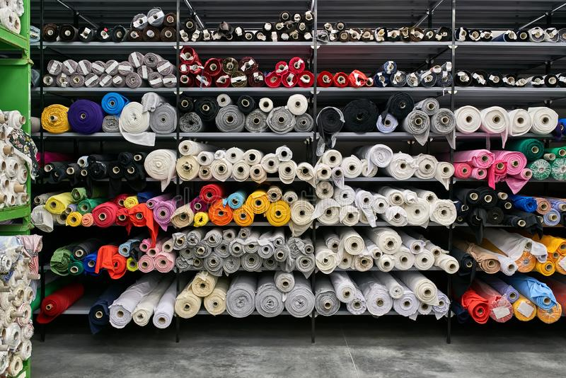 Fabric warehouse with many multicolored textile rolls stock images