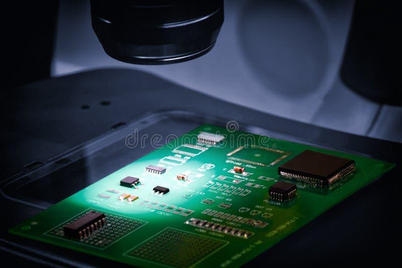 Fabricação de microplaquetas em uma placa de circuito impresso sob um microscópio fotografia de stock royalty free