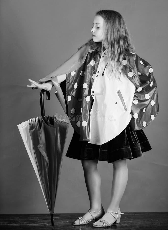 Fabricação impermeável dos acessórios Guarda-chuva colorido da posse feliz da menina da criança para vestir o casaco impermeável  foto de stock royalty free