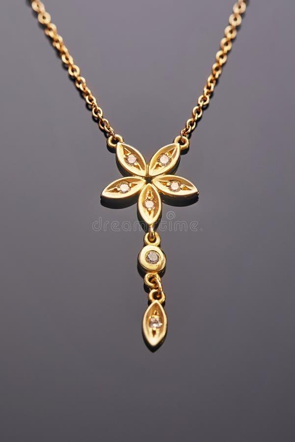 Fabricación de joyas Pendiente de oro amarillo en forma de flor de cinco hojas con diamantes en fondo gris fotografía de archivo libre de regalías