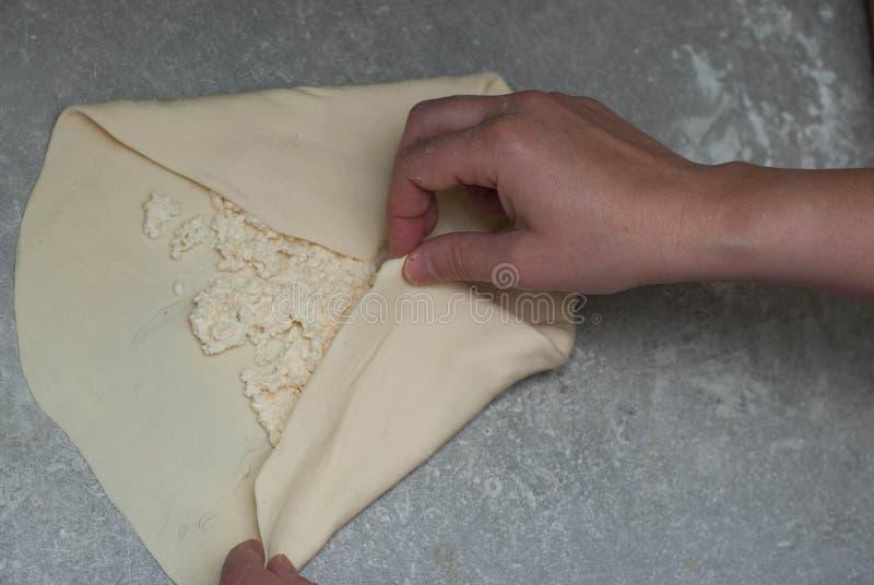 Fabricación de la empanada tradicional europea o rusa hecha en casa del queso o de la otra clase de aperitivo o de dulces de los  fotografía de archivo libre de regalías