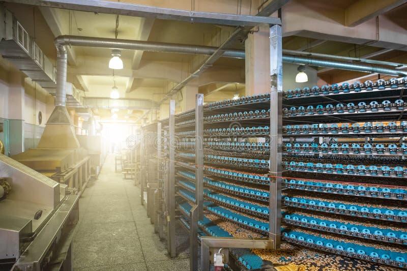 Fabricación de la fábrica de la comida, banda transportadora industrial o línea con el proceso de la preparación de galletas dulc fotografía de archivo