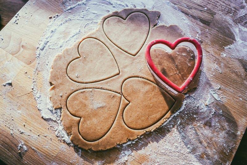 Fabricación de la galleta del corazón del pan de jengibre de la Navidad fotos de archivo libres de regalías
