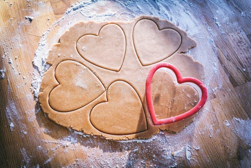Fabricación de la galleta del corazón del pan de jengibre de la Navidad fotografía de archivo libre de regalías