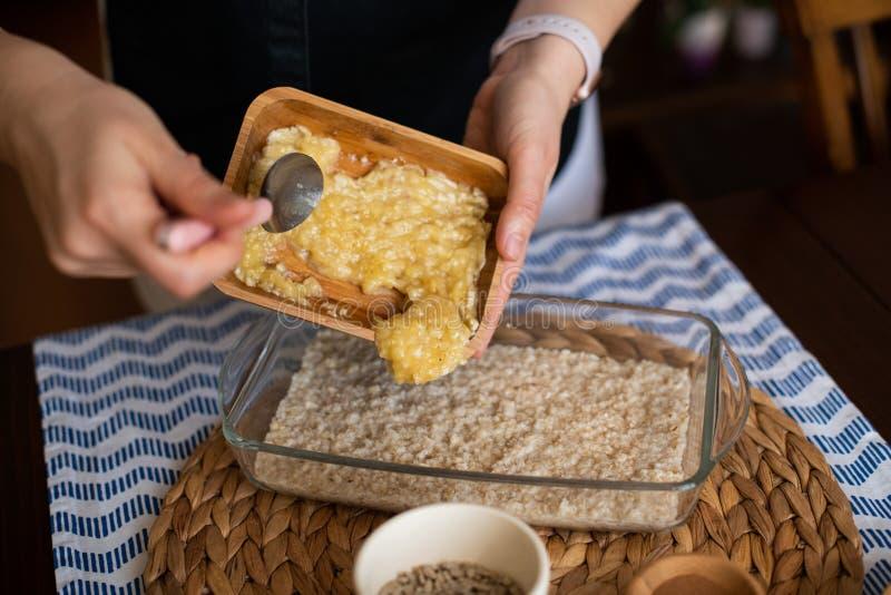 Fabricación de la harina de avena cocida con el plátano, los arándanos, la nuez y las pasas preparación de la comida para cocer C imagen de archivo