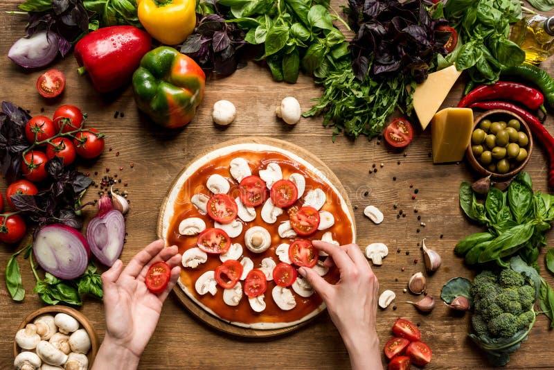 Fabricación de la pizza hecha en casa con los ingredientes frescos fotografía de archivo