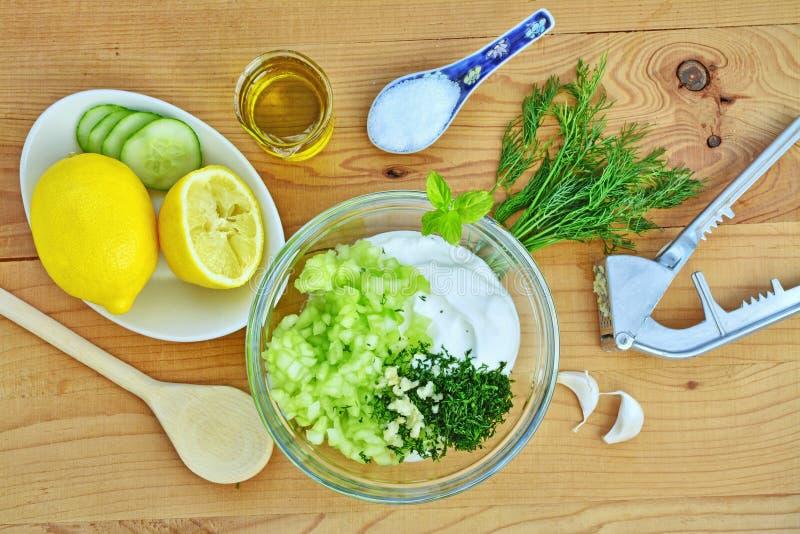 Fabricación de la salsa de Tzatziki Ingredientes griegos de la inmersión del pepino del yogur imágenes de archivo libres de regalías