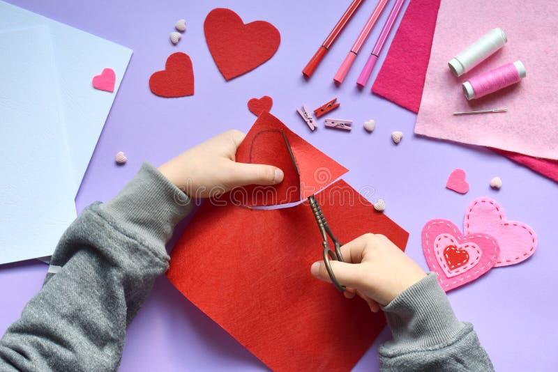 Fabricación de la tarjeta de felicitación hecha a mano de la tarjeta del día de San Valentín del fieltro El DIY de los niños, con foto de archivo libre de regalías