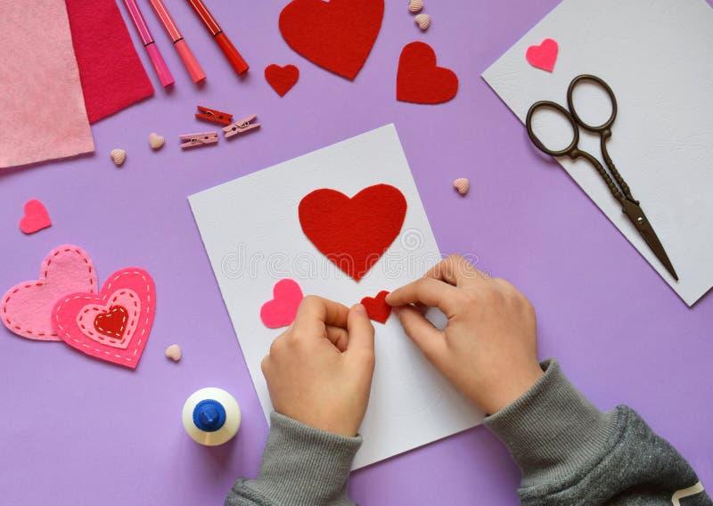 Fabricación de la tarjeta de felicitación hecha a mano de la tarjeta del día de San Valentín del fieltro El DIY de los niños, con imagen de archivo libre de regalías
