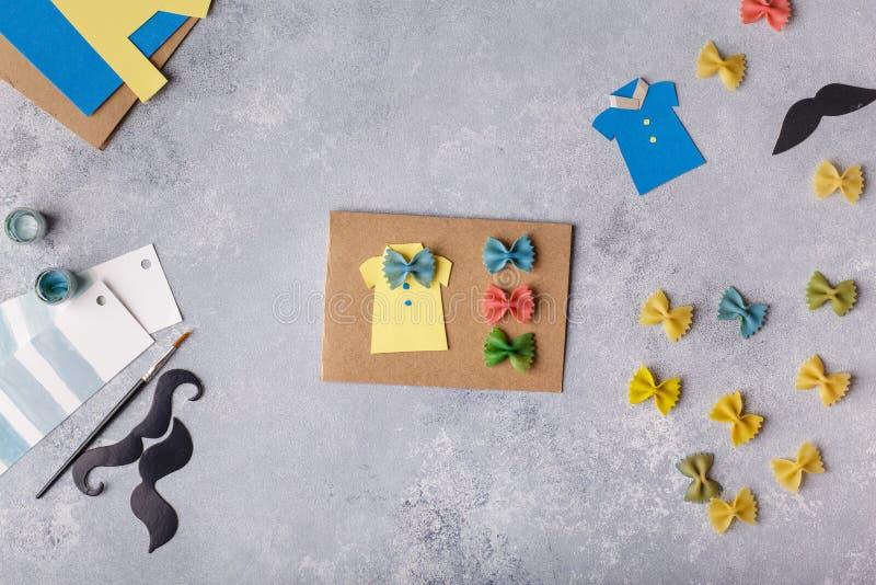 Fabricación de la tarjeta de felicitación para el día de padres Camisa con la mariposa de las pastas Tarjeta del papel bigote Pro imagen de archivo