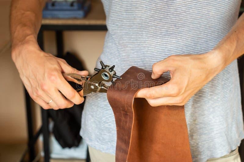 Fabricación de los agujeros con el puncher en el taller de cuero Manos masculinas con e fotografía de archivo libre de regalías
