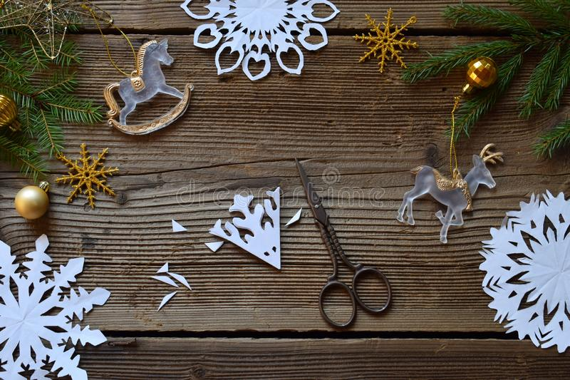 Fabricación de los copos de nieve de papel con sus propias manos Children& x27; s DIY Concepto de la Feliz Navidad y del Año Nuev fotografía de archivo libre de regalías