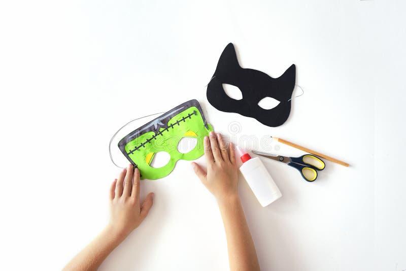 Fabricación de máscaras del papel para el día de fiesta Halloween del papel Máscara del ` s de Frankinstein y gato negro fotos de archivo libres de regalías