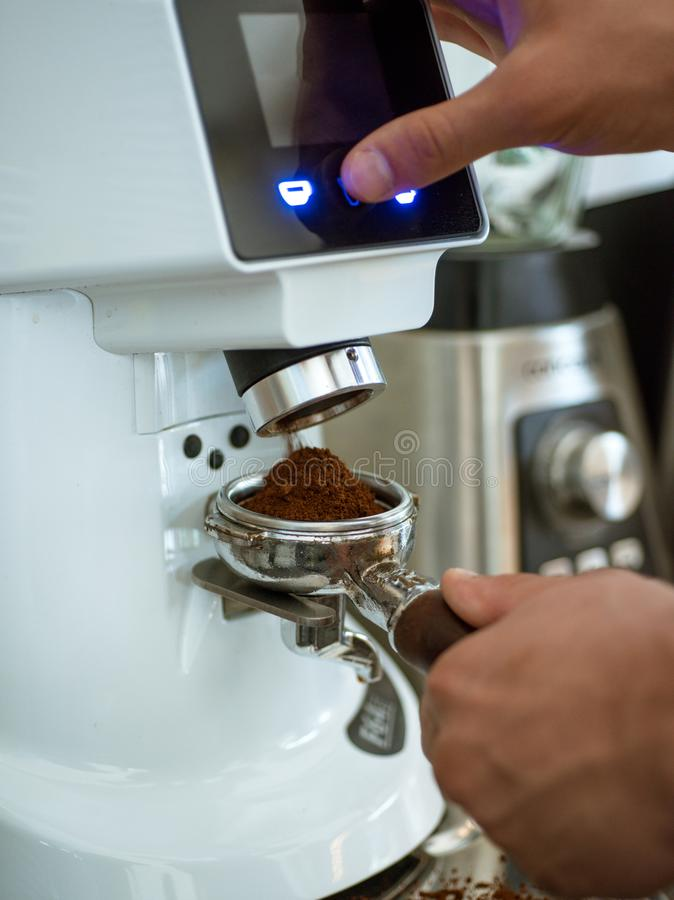 Fabricación de su taza de sorprender del gusto del café Barista hace el café express en café Amoladora de café que muele habas as fotos de archivo
