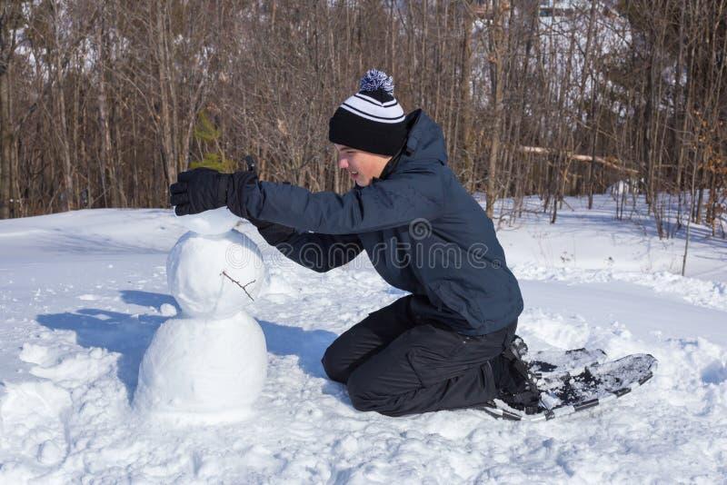 Fabricación de un muñeco de nieve imagen de archivo