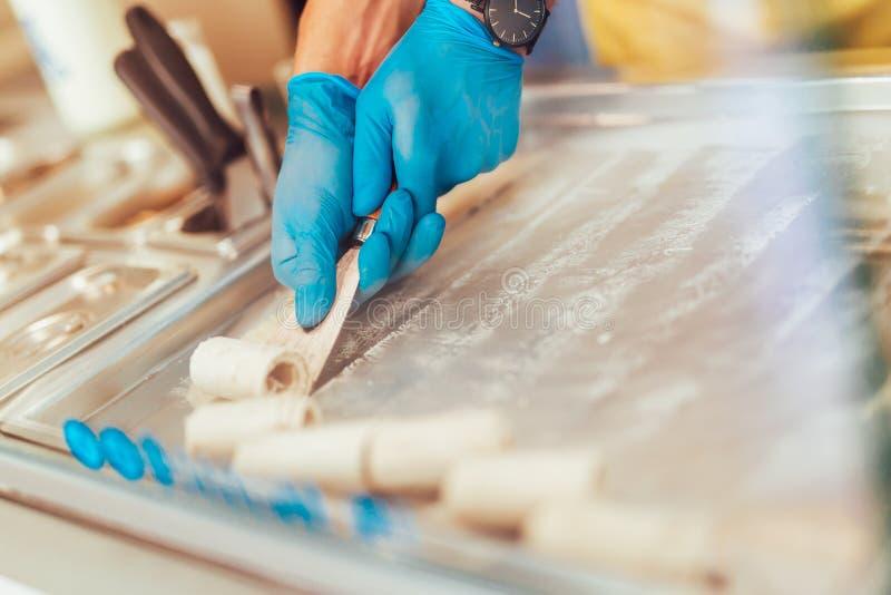 Fabricación del helado rodado en una cacerola todavía enfriada imagenes de archivo