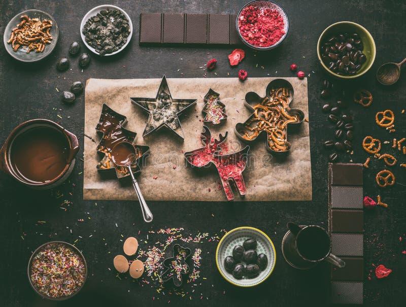 Fabricación hecha en casa de las barras de chocolate de la Navidad Cortadores de la Navidad con los diversos desmoches y condimen fotos de archivo