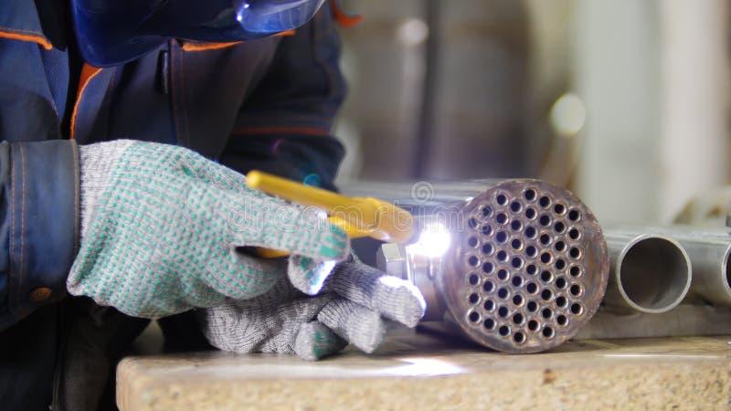 Fabricación industrial Un trabajador del hombre en tela Un detalle del hierro con pequeños agujeros en él Proceso de la soldadura fotos de archivo libres de regalías