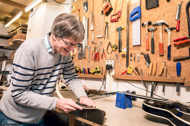 Fabricant de sourire d'instrument de musique travaillant à une guitare image libre de droits