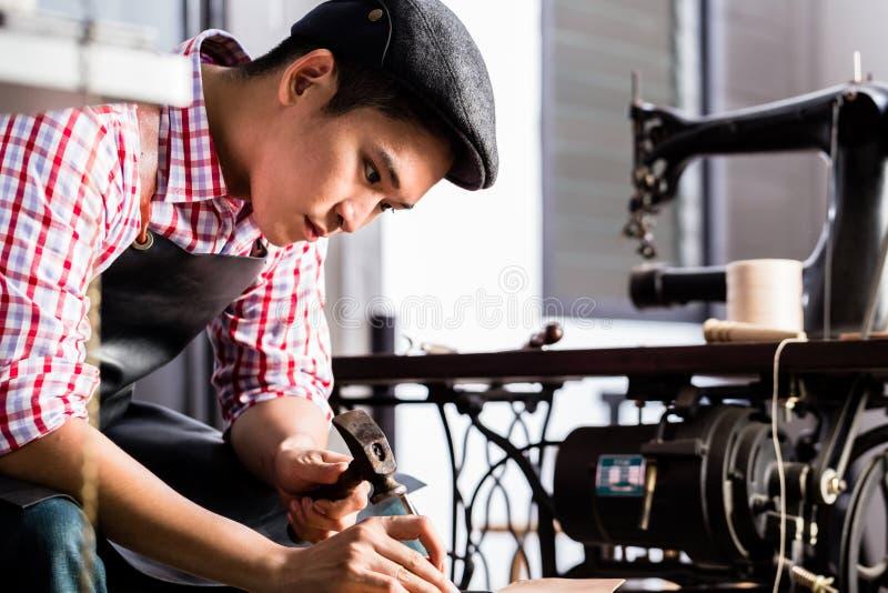 Fabricante asiático da sapata ou de correia em sua oficina de couro fotografia de stock royalty free