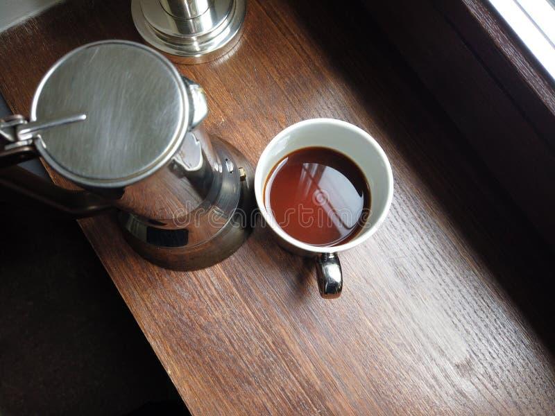 Fabricante de café de Metall y una taza de café fresco fotos de archivo