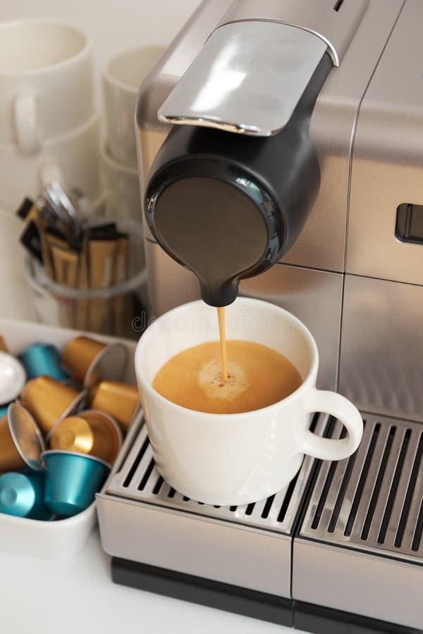 Fabricante de café moderno pequeno que derrama um copo do café do café imagem de stock