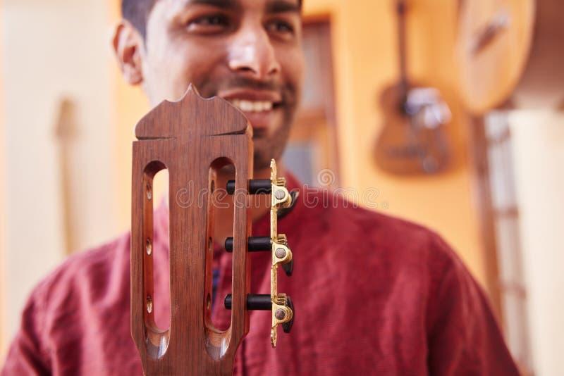 Fabricante de la guitarra con su nueva guitarra imagen de archivo