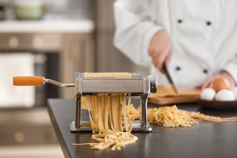 Fabricante de las pastas con pasta y el cocinero borroso en fondo foto de archivo libre de regalías