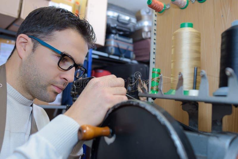 Fabricante de sapata novo que trabalha na oficina foto de stock