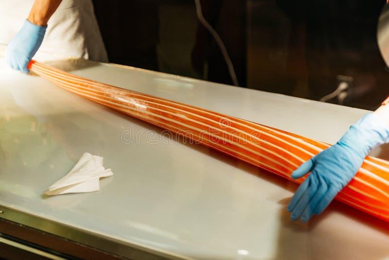 Fabricante del caramelo que rueda el caramelo anaranjado y blanco hecho a mano de la raya por las manos con los guantes en el par imagenes de archivo