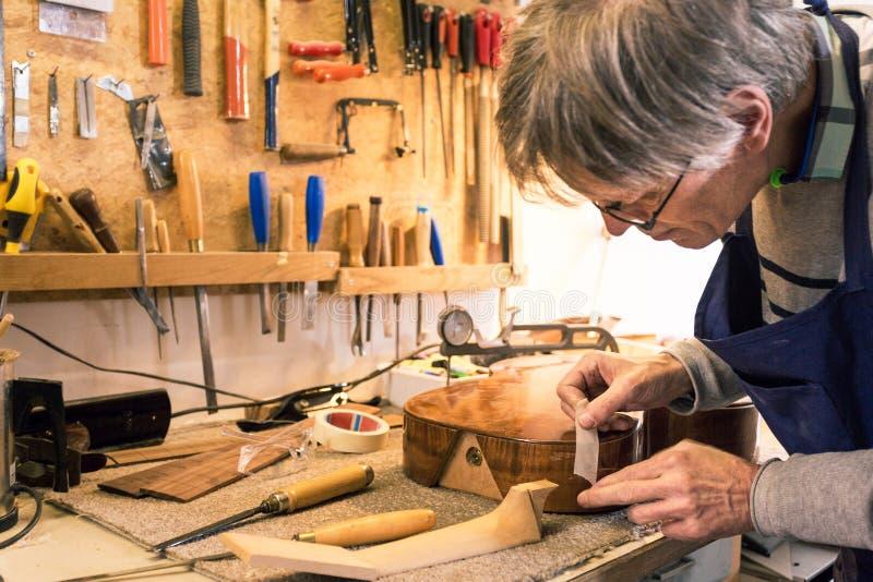 Fabricante del instrumento que enmascara una guitarra con la cinta foto de archivo libre de regalías