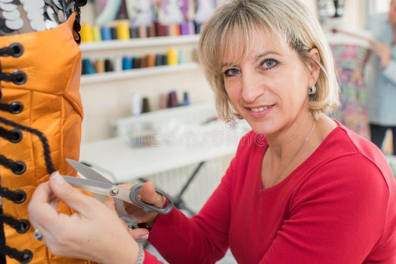 Fabricante femenino del vestido del retrato que se coloca en el taller fotografía de archivo libre de regalías