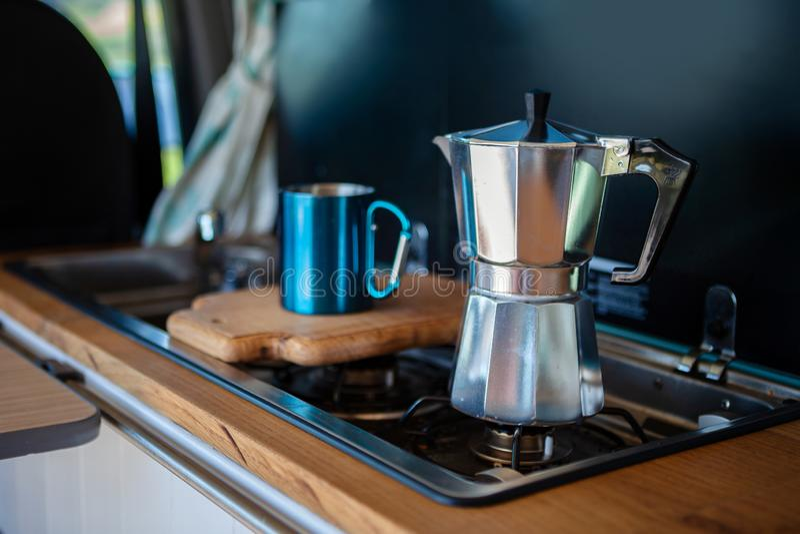 Fabricante y taza de café del stovetop de Aqua Bialetti, en una cocina de gas de la furgoneta fotografía de archivo