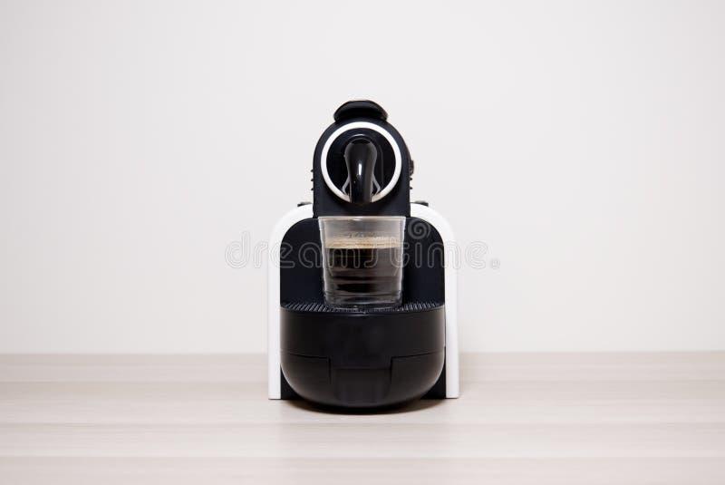 Fabricante y vidrio de la máquina de la cápsula del café express del café contra fondo neutral llano foto de archivo libre de regalías