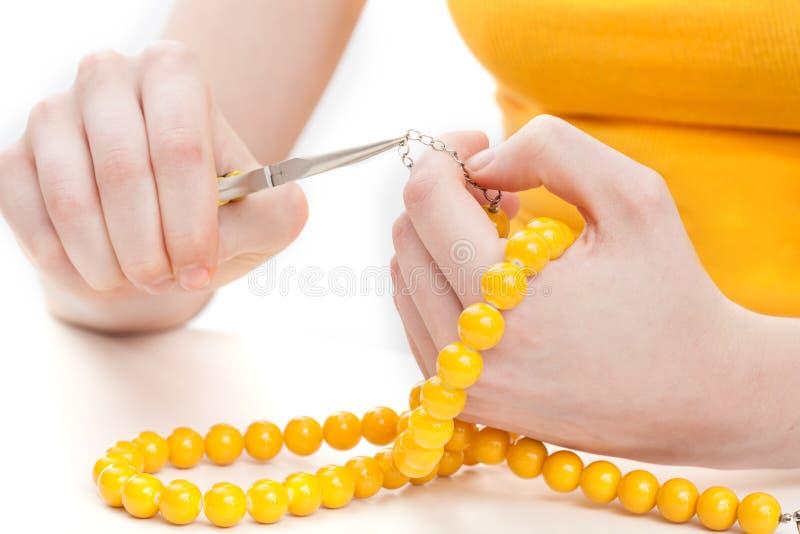 Fabrication d'un collier jaune images stock