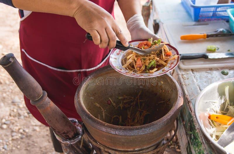 Fabrication de la salade de papaye dans un mortier, tam de som, nourriture thaïlandaise de rue, image stock