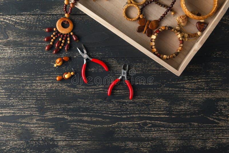 Fabrication des bijoux faits main Boîte avec des perles sur la vieille table en bois Vue supérieure avec des mains de femme photos libres de droits