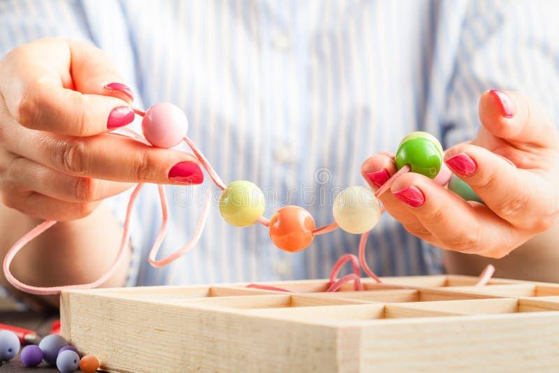 Fabrication des bijoux faits main Femme essayant un bracelet fait maison photo libre de droits