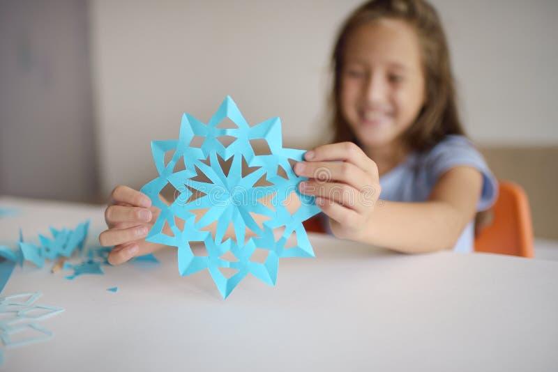 Fabrication des flocons de neige à partir du papier bleu images libres de droits