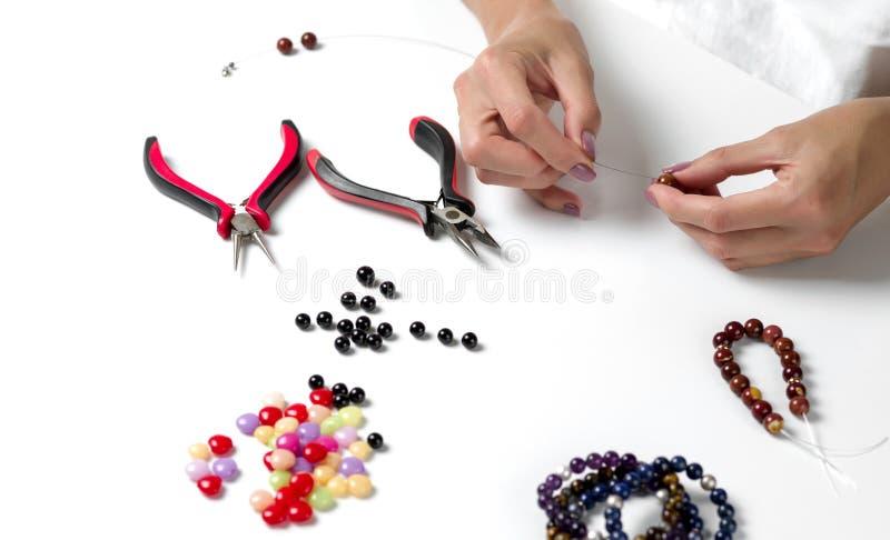 Fabrication du bracelet des perles colorées Mains femelles avec un outil sur un fond blanc photographie stock