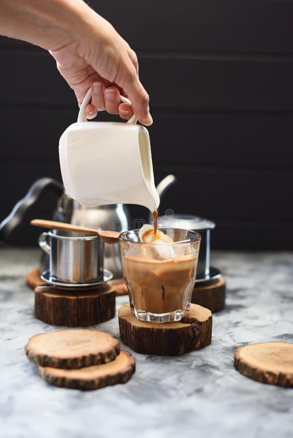 Fabrication du café glacé avec le style vietnamien de lait de noix de coco Café se renversant de main de femme sur la glace sur l photographie stock libre de droits