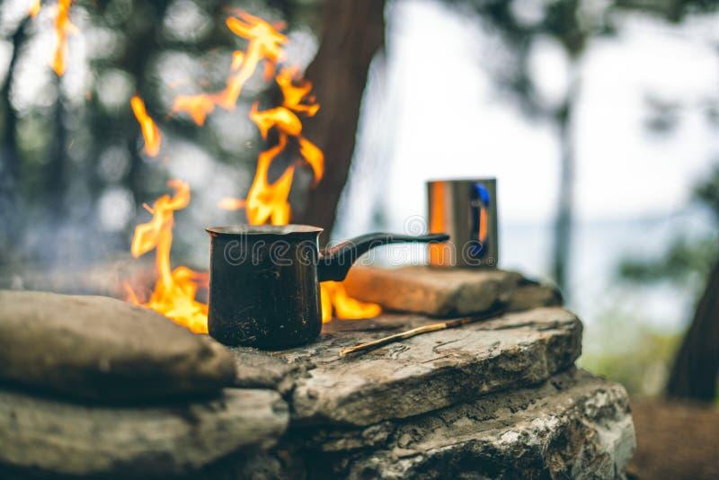 Fabrication du caf? dans le cezve sur la chemin?e en campant ou hausse caf? sur le feu de camp photographie stock libre de droits