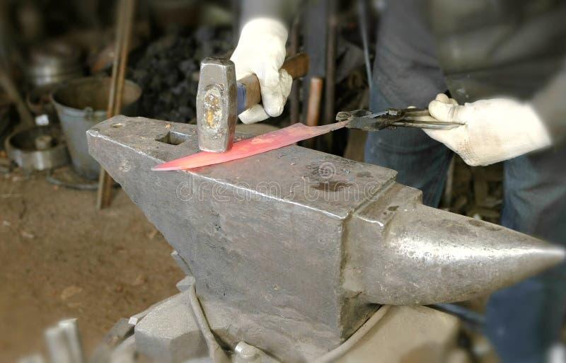 Fabrication du couteau hors du métal à la forge Fermez-vous vers le haut de frapper de mains du ` s de forgeron à fonte avec un m photographie stock libre de droits